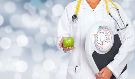Foto de Doctor woman hands with scales and apple over health care background. - Imagen libre de derechos