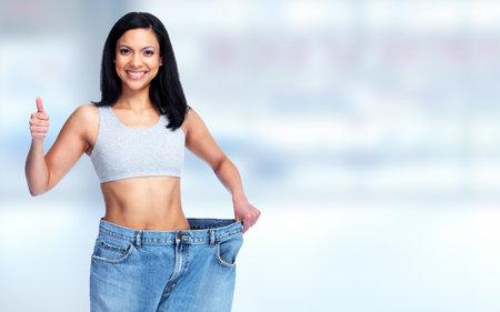 Photo pour Slimming woman abdomen with big pants over blue background. - image libre de droit