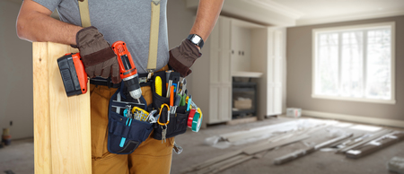 Photo for Builder handyman with construction tools on house background. - Royalty Free Image