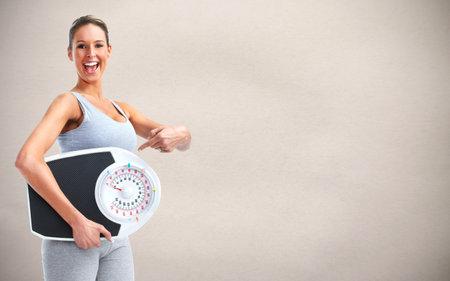 Photo pour Healthy woman with scales over gray background. - image libre de droit