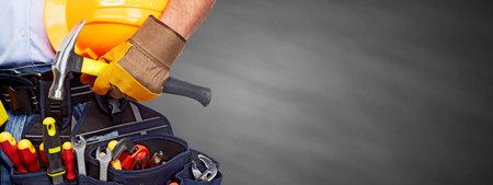 Photo pour Builder handyman with construction tools on gray background. - image libre de droit