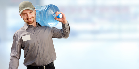 Water delivery service man with big bottle over blue background.