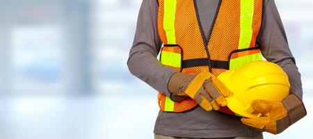 Photo pour Construction worker with helmet in orange security vest. - image libre de droit