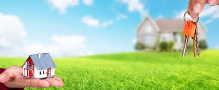 Foto de Hand with a small house and keys. Construction and real estate concept. - Imagen libre de derechos