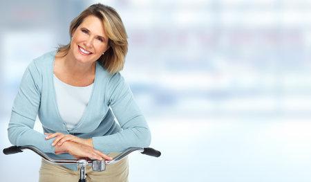 Foto de Beautiful senior woman with bicycle over blurred background. - Imagen libre de derechos