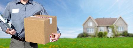 Photo pour Hands of professional postman with a box over house background. - image libre de droit