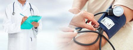 Photo pour Senior man measuring his blood pressure at clinic. - image libre de droit