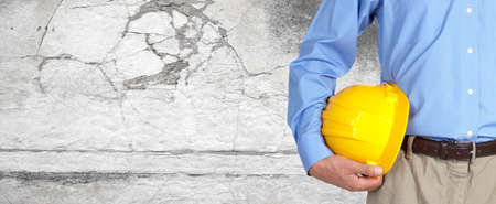 Photo pour Construction worker with helmet over gray wall background. - image libre de droit