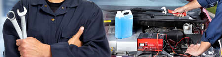 Photo pour Hands of car mechanic with wrench and car battery charger. - image libre de droit