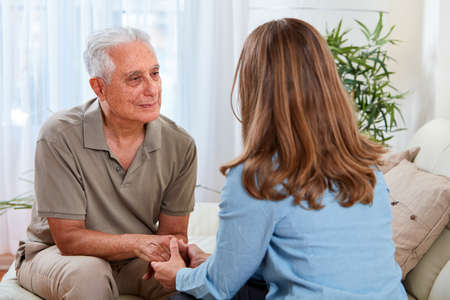 Photo for Old aged senior man talking with social worker woman at home. - Royalty Free Image