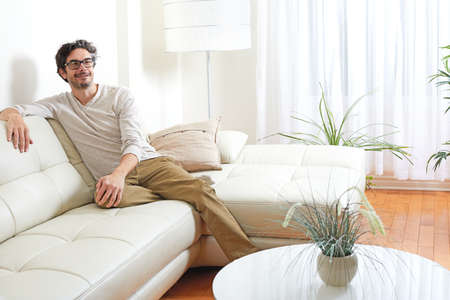 Handsome man relaxing at cozy modern living room home.