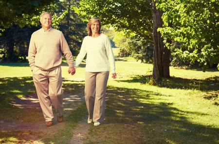 Foto de Happy loving elderly couple walking in the park. - Imagen libre de derechos