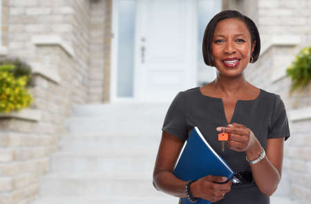 Photo for Smiling afro american real estate agent woman with house key. - Royalty Free Image