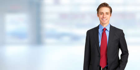 Foto per Young handsome caucasian business man over blue office, background - Immagine Royalty Free