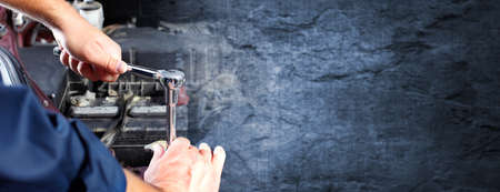Photo pour Hands of car mechanic with wrench over dark wall background. - image libre de droit