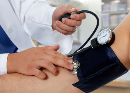 Photo for Doctor measuring blood pressure with sphygmomanometer - Royalty Free Image