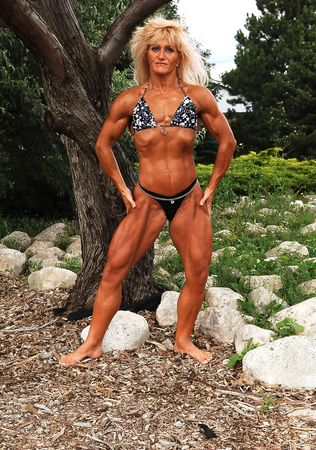 An blond bodybuilding woman standing on some rocks in front of trees in a park, shooing her good trained and lean body.