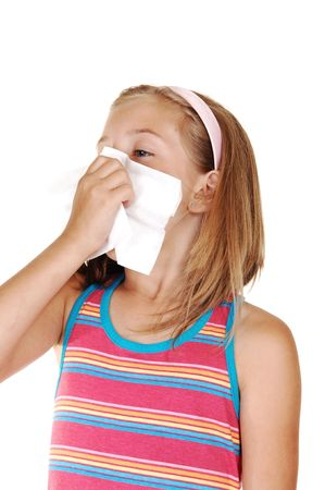 A beautiful young blond girl is sneezing in her tissue because of her cold, over white background.