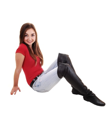 A beautiful young girl sitting on the floor in long boots and jeans and a red sweater, with her long brunette hair, over white.