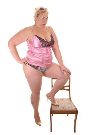 An big overweight woman in pink lingerie standing, with one leg on a  chair, in the studio, for white background.