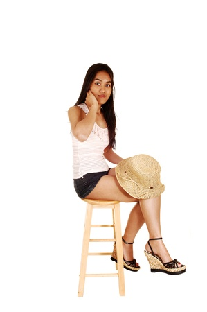 A slim and young Asian woman sitting on a chair in shorts and whitetop, holding a straw hat in her hand, for white background