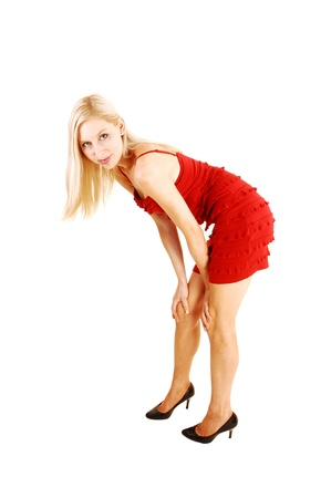 A lovely and tall blond woman standing in a red dress and high heels inthe studio for white background and bending down