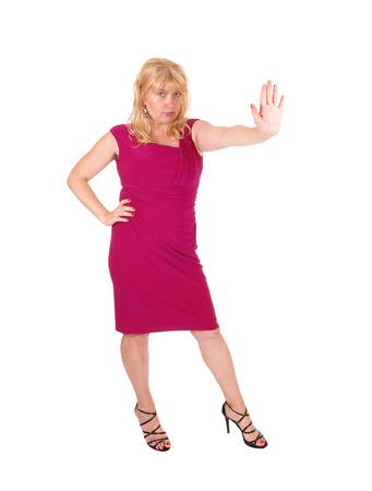 A tall blond woman in a red dress standing from front holding her handup and say's stop, isolated for white background.