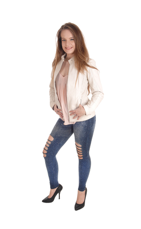Foto de A portrait image of a beautiful young woman in jeans and a white  leather jacket standing isolated for white background - Imagen libre de derechos