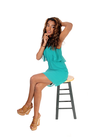 Foto de A beautiful slim woman in a short dress sitting isolated on hair with her long curly brunette hair, with hands on head, isolated white background - Imagen libre de derechos