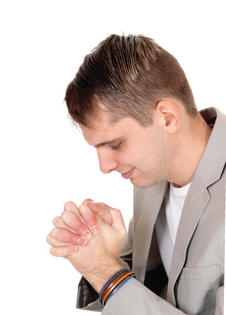 Photo for A close up image of a young man in a gray jacket sitting and praying to God with his eyes closed and hands folded, isolated over white - Royalty Free Image