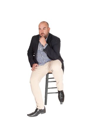 Photo pour A puzzled middle age business man sitting on a chair with his hand on his chin, looking for a solution for his problem, isolated for white background - image libre de droit