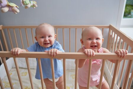 Foto de Children twins boy and girl are smiling while standing in the crib - Imagen libre de derechos