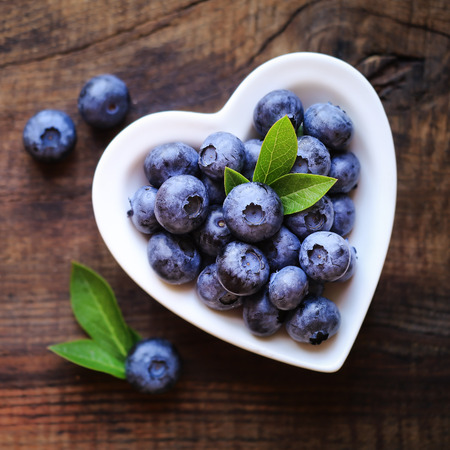 Fresh ripe garden blueberries in a white heart shape bowl on dark rustic wooden table. with copy space for your text
