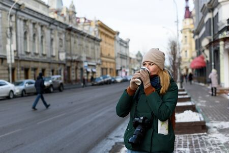 Photo pour Girl in winter clothes with camera and map in the historical center of the city is holding a cup of coffee on the street - image libre de droit