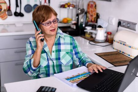 Photo for A 65-year-old woman works at home online by laptop and talks via phone because of the corona virus pandemic, more companies in are relying on the home office for their employees. - Royalty Free Image