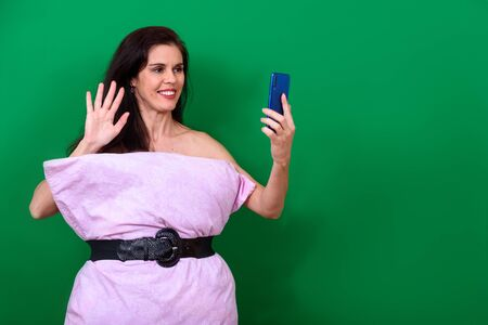 Photo for Smiling girl on a green background talks on the phone during coronavirus isolation. Challenge pillow dress. Free space for text. - Royalty Free Image