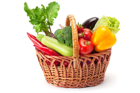 fresh and ripe vegetables arranged in a basket isolated on whiteの写真素材