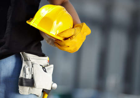 Photo for builder with yellow helmet and working gloves on building site - Royalty Free Image