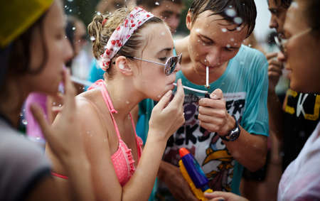 wet girls and young man taking a break and smoking a cigarettes. Photo taken in Samara city,Russia during a Water Wars flashmob