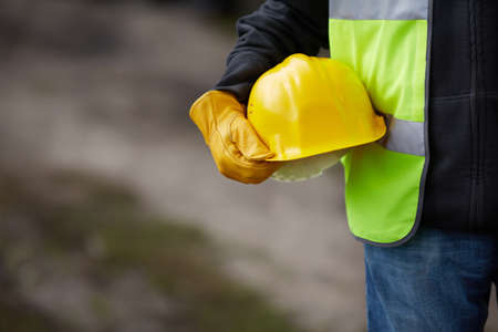 Photo pour builder with yellow helmet and working gloves on building site - image libre de droit