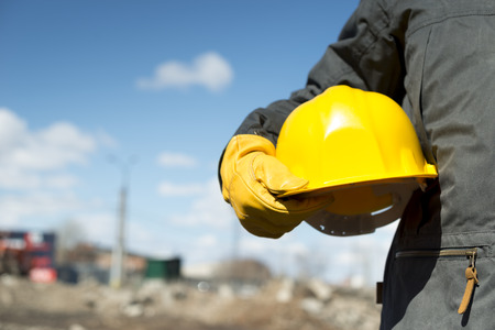 Photo pour builder with yellow hardhat and gloves, selective focus - image libre de droit