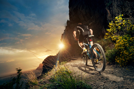 Photo pour Cyclist riding mountain bike on trail at evening. - image libre de droit