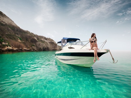 Beautiful young woman sitting on the boat a sunny summer day. Luxury vacation at sea.