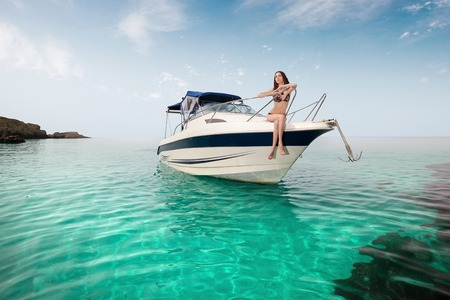 Photo pour young beautiful girl sitting on a yacht at sea. Relaxing on the water - image libre de droit