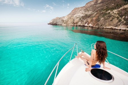 Beautiful girl sitting on a yacht at sea. Woman resting on the water