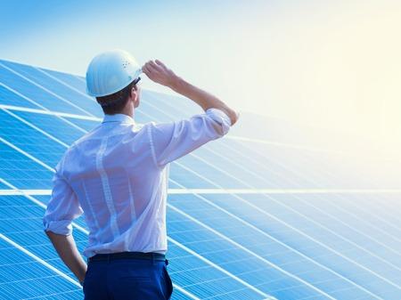 Photo pour Solar power plant. Man standing near solar panels. Renewable energy. - image libre de droit