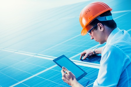 Engineer solar photovoltaic panels station checks with tablet computer.
