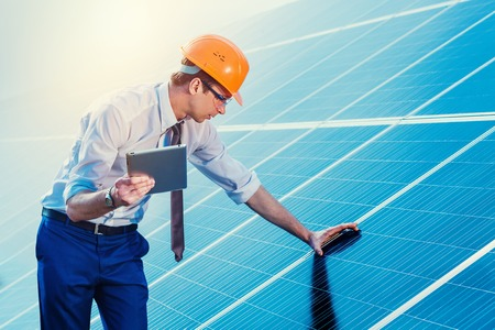 Photo for Engineer at solar power station with solar panel tablet checks. - Royalty Free Image