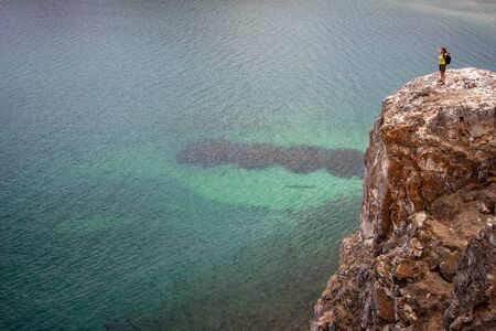 Foto für A girl with arms spread stands on a high rock near Lake Baikal with green transparent water. Steep rock with stones. The water is calm. An accumulation of algae is visible through the water. Copy space. - Lizenzfreies Bild