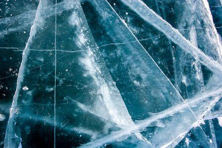 Foto de The natural texture of the transparent ice of Lake Baikal with deep cracks. Beautiful winter background. - Imagen libre de derechos